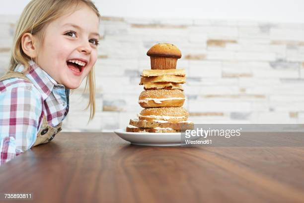 Portrait of smiling little girl with stack of baked goods