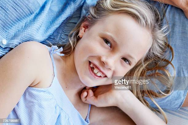 Portrait of smiling little girl with tooth gap lying on mothers lap