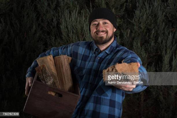 Portrait Of Smiling Lumberjack Holding Wood And Crate Against Trees At Forest