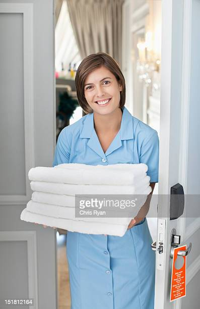 portrait of smiling maid with towels in hotel room doorway - doorway stock pictures, royalty-free photos & images