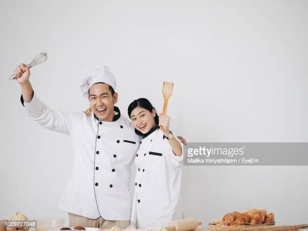 Portrait Of Smiling Male And Female Chef Against White Background