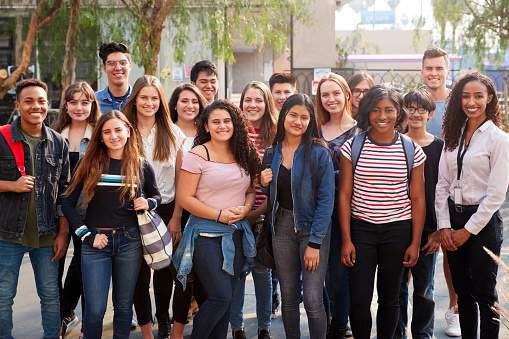 Portrait Of Smiling Male And Female College Students With Teachers Outside School Building 1133755112