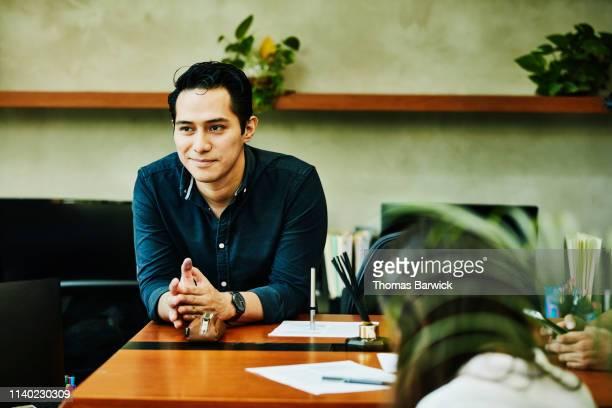 portrait of smiling male architect leaning on desk in studio - métier du design photos et images de collection