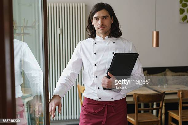 Portrait of smiling male chef standing by glass door