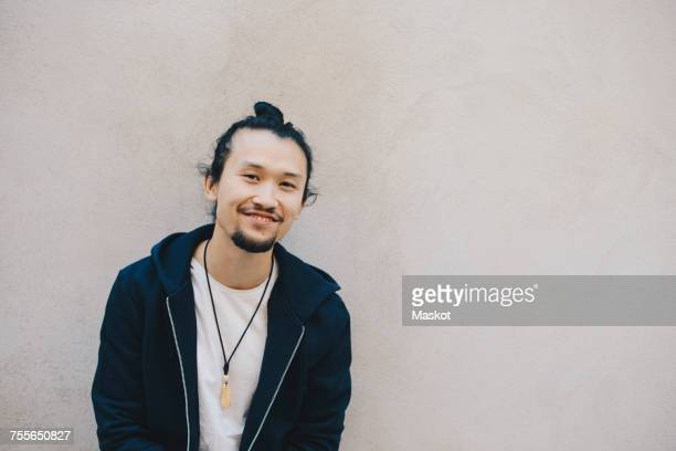 portrait of smiling male computer programmer against beige wall in office - man bun stock pictures, royalty-free photos & images
