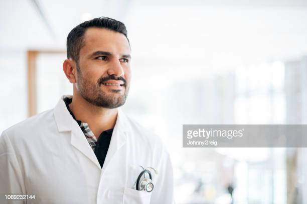 portrait of smiling male doctor in lab coat - handsome doctors stock pictures, royalty-free photos & images