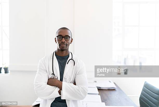 portrait of smiling male doctor standing in office - blouse photos et images de collection
