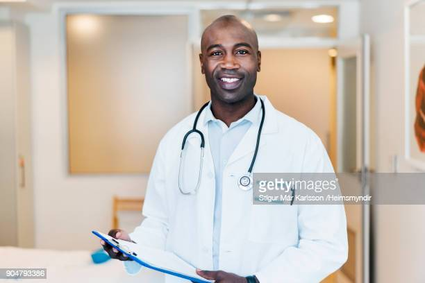 Portrait of smiling male doctor with clipboard