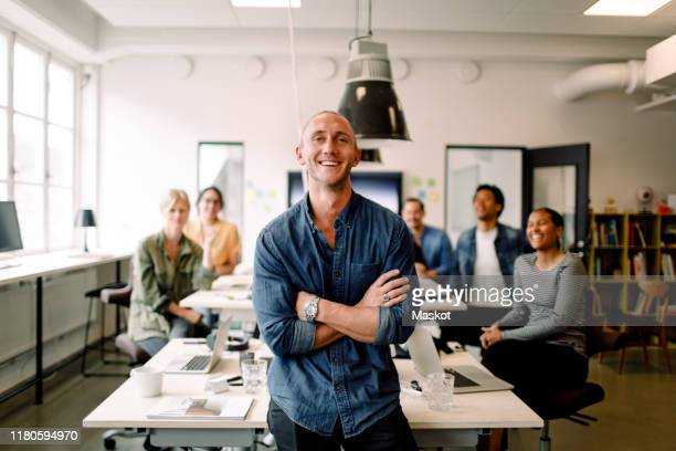 portrait of smiling male entrepreneur standing with arms crossed and employees sitting at office desk - foco diferencial imagens e fotografias de stock