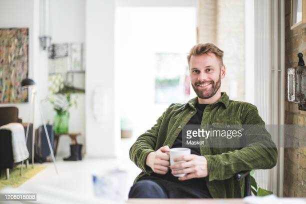portrait of smiling male entrepreneur with cup sitting at home office - 40 44 jahre stock-fotos und bilder
