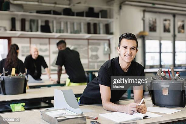 Portrait of smiling male mechanic at table with coworkers in background