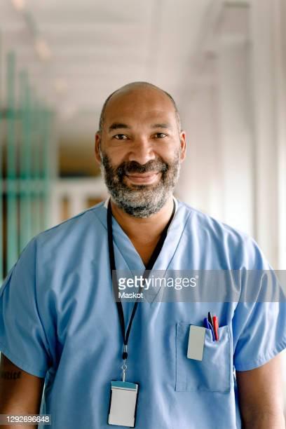 portrait of smiling male nurse in hospital corridor - arts culture and entertainment stockfoto's en -beelden