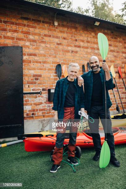 portrait of smiling male owner with oar by senior friend standing against house - disruptaging stock pictures, royalty-free photos & images
