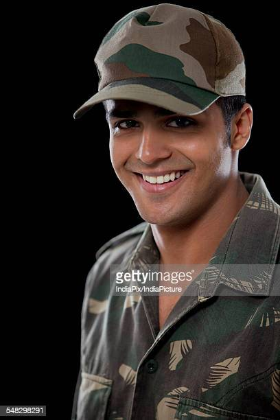 Portrait of smiling male soldier over black background