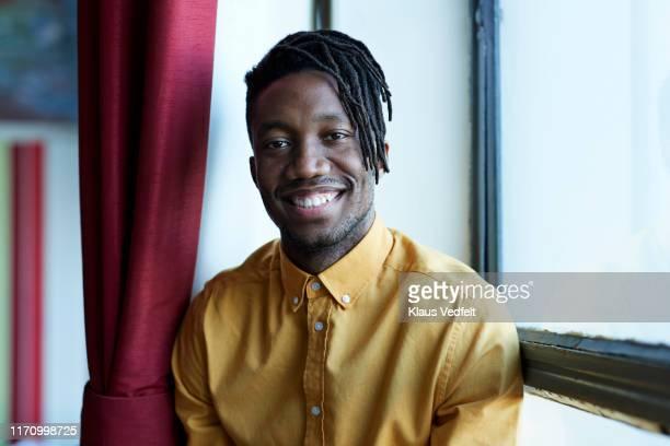 portrait of smiling male student sitting by window - belle black photos et images de collection