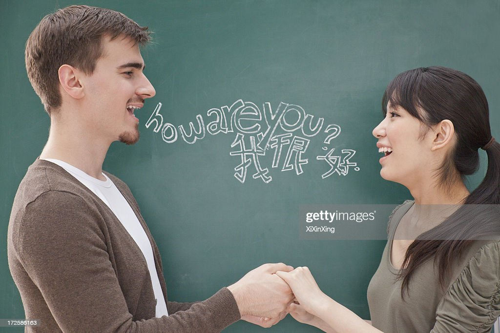 Portrait of smiling male teacher and student in front of chalkboard holding hands : Stock Photo