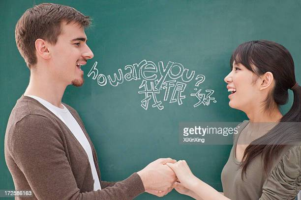 portrait of smiling male teacher and student in front of chalkboard holding hands - scrittura non occidentale foto e immagini stock