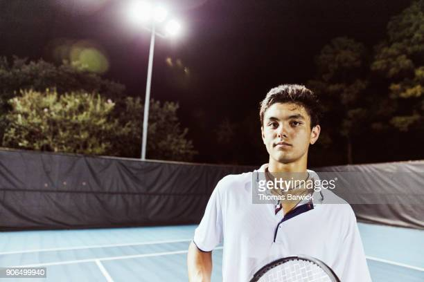 Portrait of smiling male tennis player standing on court at night