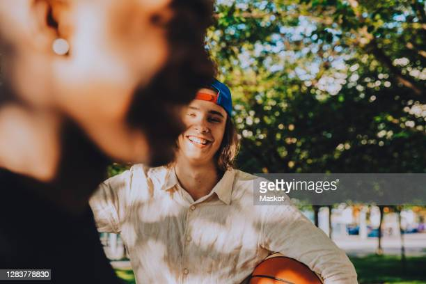 portrait of smiling male with friend holding soccer ball in park - generation z stock pictures, royalty-free photos & images