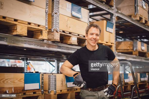 Portrait of smiling male worker standing against rack at warehouse