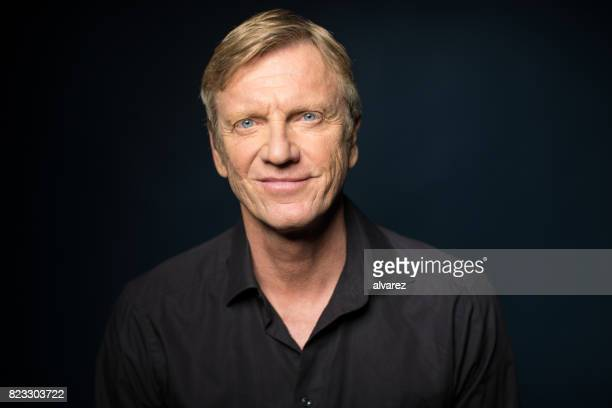 portrait of smiling man against black background - black shirt stock pictures, royalty-free photos & images