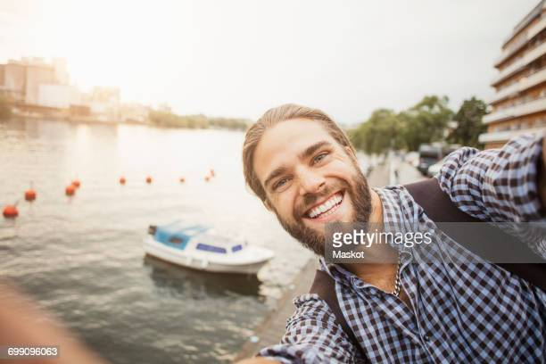 portrait of smiling man against boat moored at river in city - self portrait photography stock pictures, royalty-free photos & images