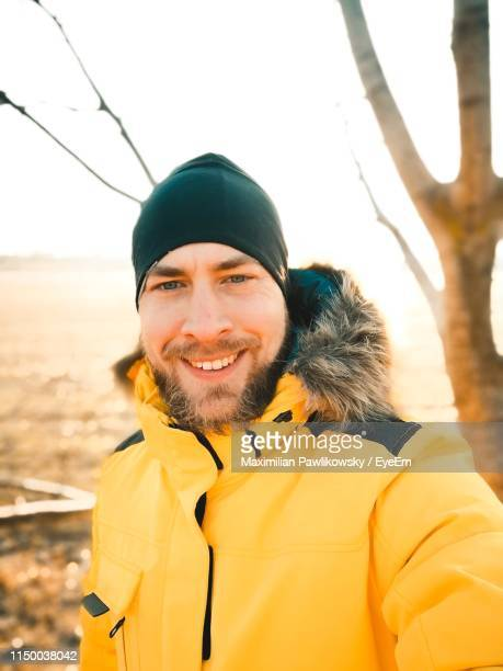 portrait of smiling man against sky during winter - einzelner mann über 30 stock-fotos und bilder