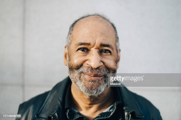 portrait of smiling man against wall - senior men stock pictures, royalty-free photos & images
