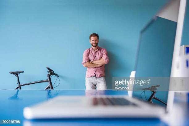 portrait of smiling man and laptop in break room of modern office - focus on background stock pictures, royalty-free photos & images