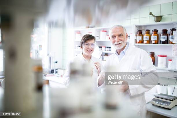 portrait of smiling man and woman in laboratory of a pharmacy - focus on background stock pictures, royalty-free photos & images