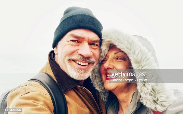 portrait of smiling man and woman in winter - hastings stock photos and pictures