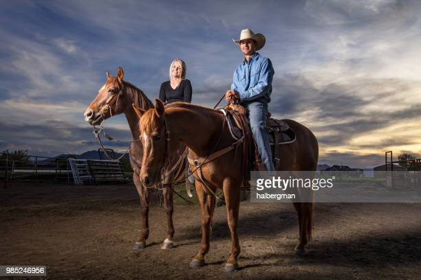 Portrait of Smiling Man and Woman on Horseback at Sunset
