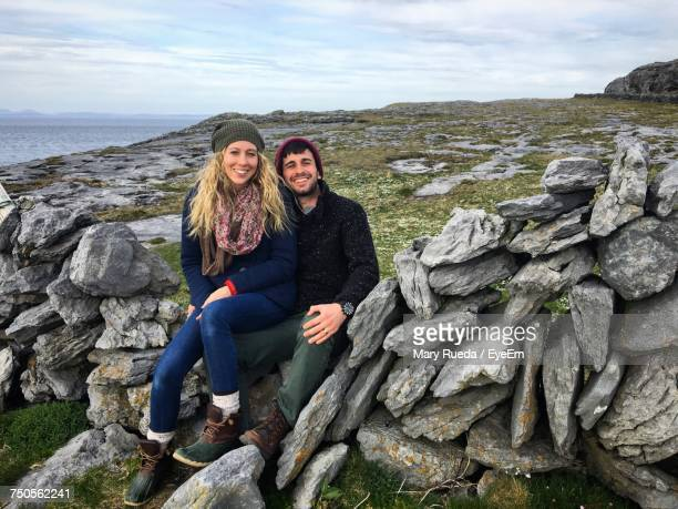 portrait of smiling man and woman sitting on rocks against cloudy sky - irlande photos et images de collection