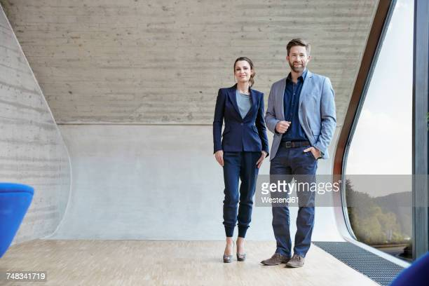 portrait of smiling man and woman standing in attic office - 40 44 jahre stock-fotos und bilder