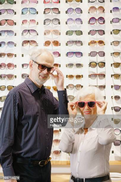Portrait of smiling man and woman wearing sunglasses while standing at store