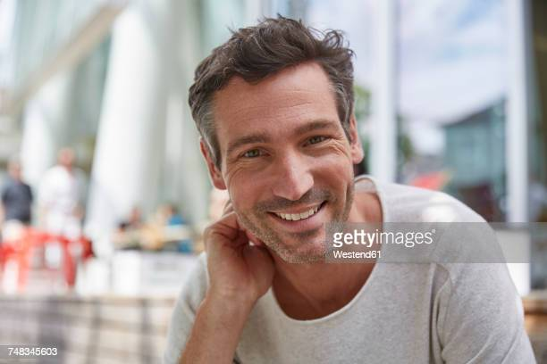 portrait of smiling man at an outdoor cafe - mann stock-fotos und bilder