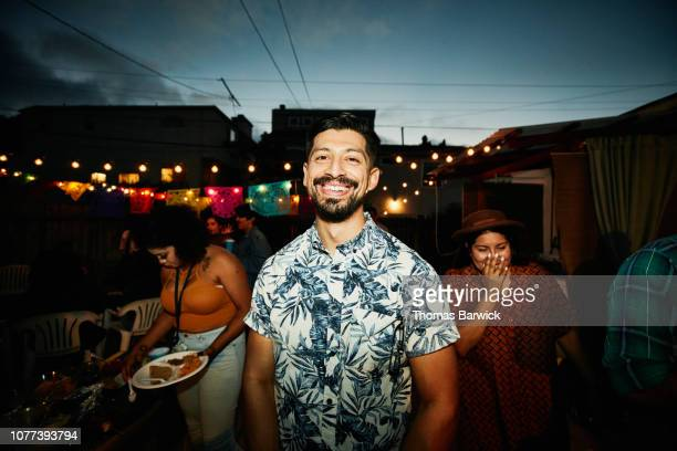Portrait of smiling man at backyard party with friends on summer evening