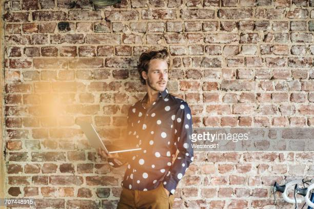 Portrait of smiling man at brick wall using laptop