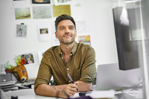 Portrait of smiling man at desk in his office - gettyimageskorea