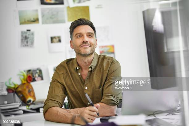 Portrait of smiling man at desk in his office