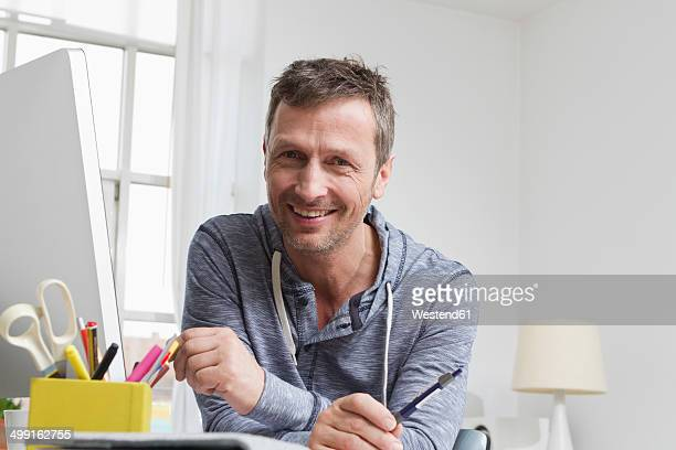 Portrait of smiling man at desk