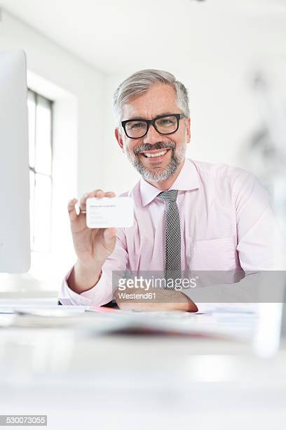 Portrait of smiling man at desk showing his business card