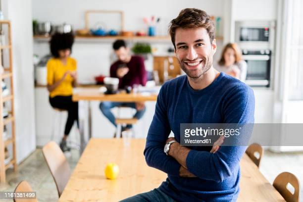 portrait of smiling man at dining table at home with friends in background - premier plan net photos et images de collection