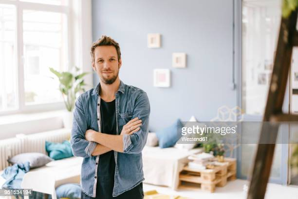 portrait of smiling man at home - zufriedenheit stock-fotos und bilder