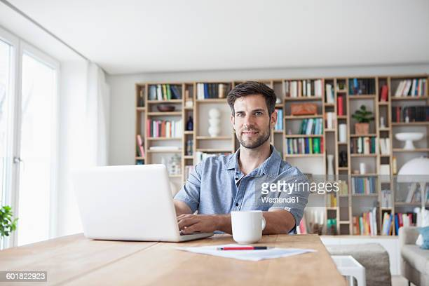 portrait of smiling man at home using laptop - hommes d'âge moyen photos et images de collection