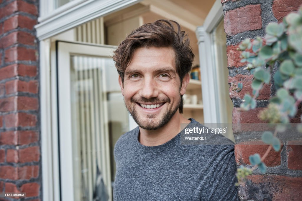 Portrait of smiling man at house entrance : Stock Photo