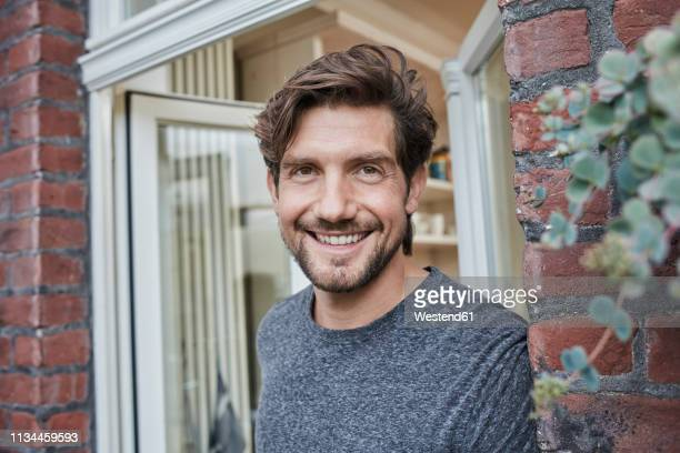 portrait of smiling man at house entrance - einzelner mann über 30 stock-fotos und bilder