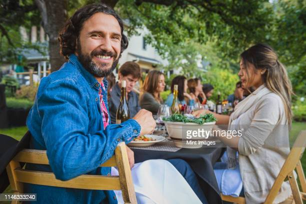 portrait of smiling man at party outdoors - fish love stock pictures, royalty-free photos & images