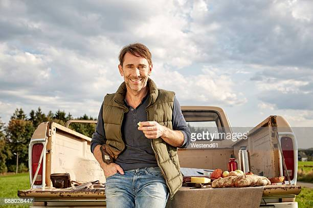Portrait of smiling man at pick up truck having picnic