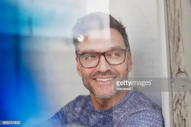 portrait of smiling man behind glass pane wearing glasses - sonrisa con dientes fotografías e imágenes de stock
